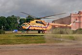Orange Russian Mi-8 Helicopter Is Landing On Grass Lawn.