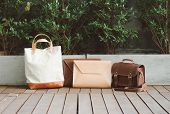stock photo of wood craft  - Fashion Leather Bags on wood deck with Nature Background