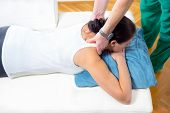 stock photo of chiropractor  - Chiropractor adjusting neck muscles on female patient - JPG