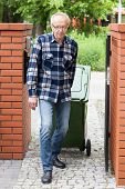 stock photo of dumpster  - Elderly man pulling a wheeled dumpster vertical - JPG