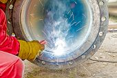 foto of pipe-welding  - Welder welding a pipe on a terrain