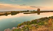 stock photo of ferrara  - landscape at sunset of the swamp with ruins of an old house - the lagoon in the natural reserve of Comacchio Ferrara Italy