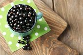 picture of mug shot  - Ripe blackcurrants in mug on board - JPG