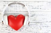 foto of heart sounds  - Headphones and heart on wooden background - JPG