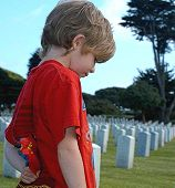 stock photo of inhumane  - Child in military cemetery holding superman toy - JPG