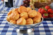 image of cream puff  - A silver bowl of vanilla cream puffs and strawberries