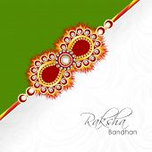 pic of rakhi  - Beautiful golden rakhi on green and floral decorated grey background for Raksha Bandhan celebrations - JPG