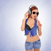 stock photo of licking  - Sexy young woman licking lollipop while listening to the music on headphones - JPG