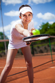 foto of youg  - Youg pretty girl playing tennis on cort