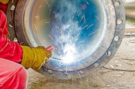 foto of pipe-welding  - Welder welding a pipe on a terrain  - JPG