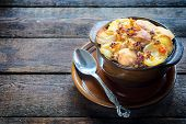 foto of baked potato  - Moussaka in the old brown bowl with baked potato on topselective focus and blank space - JPG