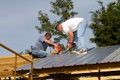 stock photo of rafters  - Two construction workers attach sheet metal to wood rafters of a barn with electric and battery powered screw guns - JPG