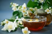 foto of jasmine  - jasmine tea in a teapot with a branch of jasmine on a wooden table