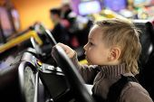 Постер, плакат: Kid Playing With Car Simulator