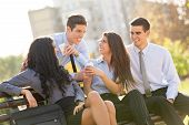stock photo of bench  - A small group of young business people during a coffee break, sitting on a park bench enjoying a coffee and a sunny day.