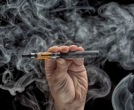 foto of e-cig  - Hand holding an electronic cigarette over a dark background - JPG