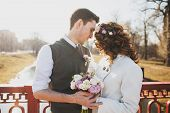 stock photo of boutonniere  - young couple holding hands - JPG