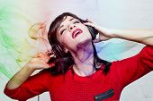 picture of red-necked  - Woman in red listening to music on headphones - JPG