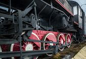 stock photo of train-wheel  - Black vintage steam railway train with red wheels close view - JPG