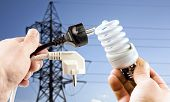 stock photo of fluorescence  - Fluorescent bulb and plug in the hands against the background of the power lines - JPG