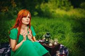 stock photo of harmony  - Beautiful red hair girl with deep green eyes sitting in grass - JPG