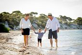 foto of father daughter  - young happy mother and father holding hands of sweet blond little daughter walking together on sand at beach sea shore enjoying summer holidays playing in family vacation lifestyle concept - JPG