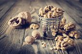 stock photo of walnut  - Walnut kernels and whole walnuts on wooden table - JPG