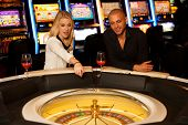stock photo of roulette table  - Young Couple Playing Roulette In Casino Betting And Winning - JPG