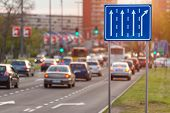 stock photo of crossroads  - Traffic with cars and bus on city boulevard towards the crossroad with green light opposite the setting sun.