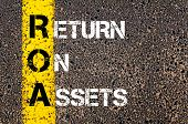 picture of asset  - Business Acronym ROA - Return on assets. Yellow paint line on the road against asphalt background. Conceptual image - JPG