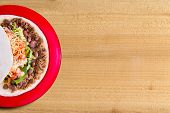 stock photo of ground-beef  - Delicious burrito filled with spicy ground beef beans and salad topped with cheese on a colorful red plate overhead view on a wood background with copyspace - JPG