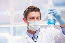 pic of beaker  - Scientist examining beaker with blue fluid in laboratory - JPG