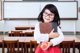 stock photo of indian apple  - Portrait of little girl back to school and standing in the classroom while wearing glasses and holding a book with apple - JPG