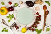 Fresh raw greens and unprocessed vegetables over rustic white background, blue plate in center, top  poster