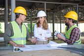 Mature Builders And Contractor Talking During Work On Construction Site poster