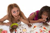 stock photo of anorexic  - Two attractive women stuffing food into their mouths on white background - JPG