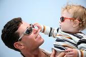 pic of father child  - father with the child in the sunglasses against the background of the sky - JPG