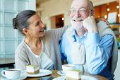 Affectionate mature woman embracing her happy husband in cafe poster