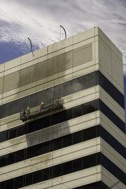 image of pressure-wash  - Window Washers Pressure Washing an Office Building - JPG