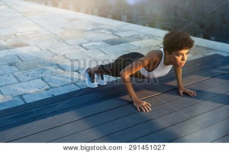 poster of Fit african girl doing pushup exercise outdoor in the city street at dusk. Brazilian fitness woman w