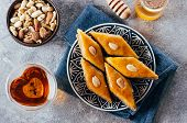 Baklava. Ramadan Dessert. Traditional Arabic Dessert With Nuts And Honey, Cup Of Tea On A Concrete T poster