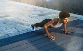 Fit african girl doing pushup exercise outdoor in the city street at dusk. Brazilian fitness woman w poster