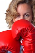 Close up of a woman who is wearing boxing gloves, white background.