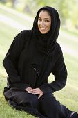 Middle Eastern Woman Sat On Grass In Park