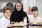 Middle Eastern Woman And Children Eating And Drinking In Shopping Mall