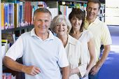 image of senior adult  - Four people in library standing by bookshelves - JPG