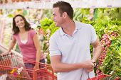 picture of grocery-shopping  - Young couple shopping for vegetables at a grocery store - JPG