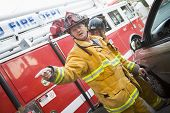 image of crew cut  - Fireman pointing at something with another fireman using the jaws of life on a car door - JPG