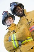 stock photo of firefighter  - Two firefighters standing outdoors wearing helmets - JPG