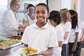 image of school lunch  - Students in cafeteria line with one holding his healthy meal and looking at camera  - JPG